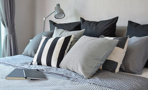 stylish bedroom interior design with black patterned pillows on